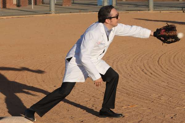 Dr. Michael Okun wears a lab coat and sunglasses while standing on a baseball field and catching a baseball in a mit.