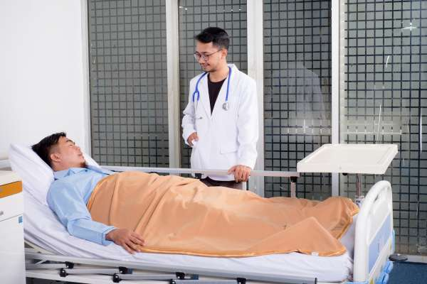 patient in a hospital bed with a doctor smiling at him