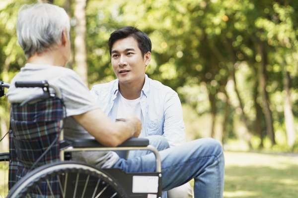 young asian adult son chatting with wheel chair bound father outdoors in park
