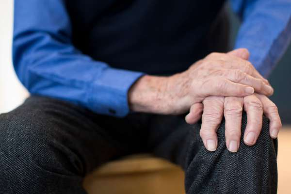 older man holding his hand down so it doesn't shake